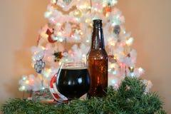 Glas Bier aufgeworfen vor Baum der weißen Weihnacht mit farbigen Lichtern lizenzfreie stockfotos