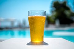 Glas Bier durch das Pool lizenzfreie stockfotos