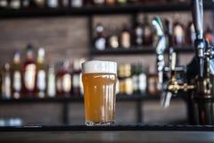 Glas bier in een bar stock afbeelding