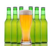 Glas Bier met erachter Flessen Stock Afbeelding