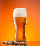 Glas bier met oranje achtergrond stock afbeelding