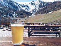 Glas Bier mit Alpenberg im Hintergrund Stockfotografie