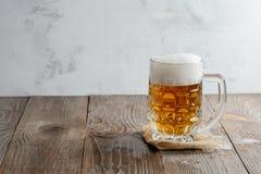 Glas Bier mit Schaum auf einem hölzernen Hintergrund Lizenzfreies Stockfoto