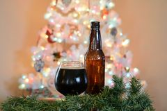 Glas bier voor witte Kerstboom met gekleurde lichten wordt gesteld dat stock foto's