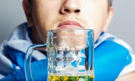 Glas Bier vor Gesicht des Mannes mit bayerischer Flagge Lizenzfreie Stockfotos