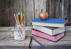 Glas Bleistiftzeichenstifte mit einem Apfel, der auf Staplungsbüchern sitzt Lizenzfreies Stockbild