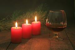Glas brandewijn of cognac en kaars op de houten lijst Vieringssamenstelling royalty-vrije stock foto