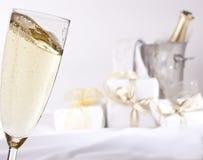 Glas Champagner und Geschenke Stockfotografie