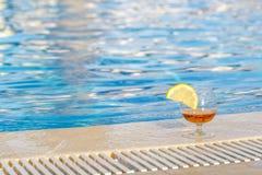 Glas cognac, een plak van citroen, blauw poolwater als attribuut van een luxueuze vakantie stock foto's