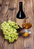 Glas cognac en bos van druiven stock foto