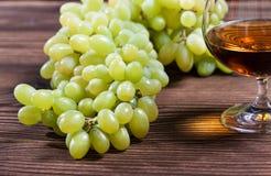 Glas cognac en bos van druiven royalty-vrije stock afbeeldingen