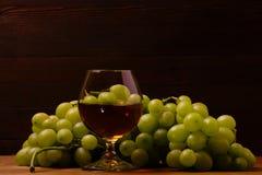 Glas cognac en bos van druiven stock fotografie