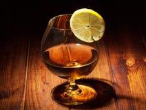 Glas cognac met citroen stock foto's