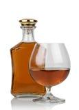 Glas cognac met fles stock afbeelding
