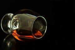 Glas cognac op een zwarte achtergrond stock foto