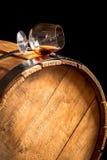 Glas cognac op het oude houten vat stock foto's