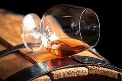 Glas cognac op het oude vat stock afbeelding