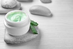 Glas Creme für den Körper und Aloe verlässt auf hellem Hintergrund Lizenzfreie Stockfotos