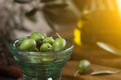 Glas cup of olives with extra virgin olive oil in glass bottle on rustic background. close up stock photos