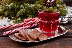 Glas de drank en de gemberkoekjes van het Amerikaanse veenbesfruit op metaalplaat over oude houten lijst Royalty-vrije Stock Fotografie