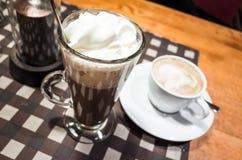Glas der heißen Schokolade und der weißen Schale Cappuccinos Lizenzfreie Stockbilder