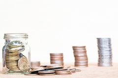 Glas der Münze und der verbreiteten Münze auf Boden auf Weinlese verwischte backgr Lizenzfreies Stockfoto