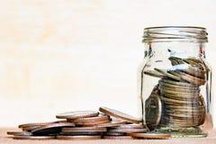 Glas der Münze und der verbreiteten Münze auf Boden auf Weinleseholz verwischte b Stockfotos