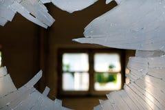 Glas der zerbrochenen Fensterscheibe, das innerhalb eines Hauses mit einem Fenster backgro schaut Stockbilder