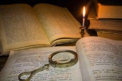 Glas des alten Buches und des Vergrößerungsglases unter der hellen Kerze Lizenzfreie Stockfotos