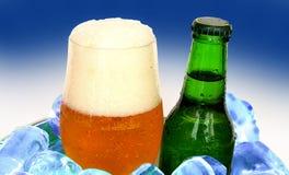 Glas des Bieres und der Flasche auf Eis Stockfoto