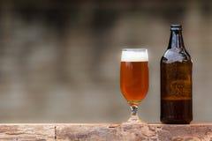 Glas des Bieres und der Flasche auf hölzerner Tabelle Stockfotografie