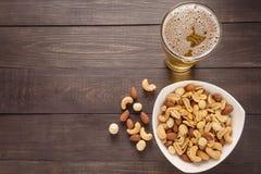Glas des Bieres und der Mandel, Macadamia, Erdnuss, Acajounuss auf dem w Stockfoto