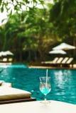 Glas des Cocktails auf sundeck am Swimmingpool lizenzfreie stockfotografie