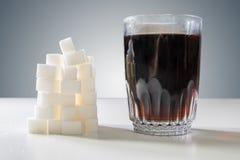 Glas des Cola und Haufen von Zucker-cubec Ungesundes Essenkonzept Stockfoto