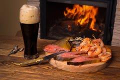 Glas des dunklen Bieres und der Fischservierplatte auf dem Hintergrund eines Büros Lizenzfreies Stockfoto