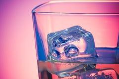 Glas des Getränks mit Eis auf Discoveilchenlicht Lizenzfreies Stockfoto