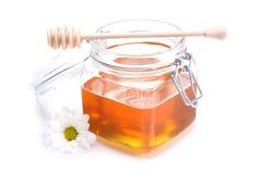Glas des Honigs, des Schöpflöffels und der Blume Lizenzfreies Stockbild