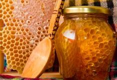 Glas des Honigs und der Bienenwabe stockfoto