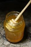 Glas des Honigs und des Stockes zum Honig auf einem hölzernen Hintergrund Stockfotografie