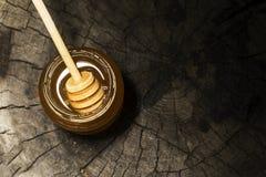 Glas des Honigs und des Stockes zum Honig auf einem hölzernen Hintergrund Stockfotos