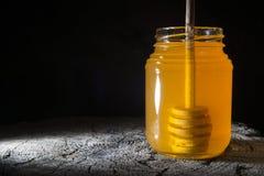Glas des Honigs und des Stockes zum Honig auf einem hölzernen Hintergrund Stockfoto