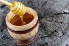 Glas des Honigs und des Stockes zum Honig auf einem hölzernen Hintergrund Lizenzfreies Stockbild