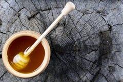 Glas des Honigs und des Stockes zum Honig auf einem hölzernen Hintergrund Lizenzfreies Stockfoto