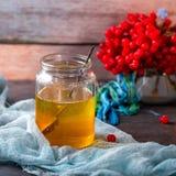 Glas des Honigs und des Viburnum auf hölzernem Hintergrund Lizenzfreies Stockfoto