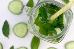 Glas des köstlichen Auffrischungssommergetränks - Cocktail von Scheiben Gurke, Eis, Minze, Stroh, Draufsicht, Nahaufnahme lizenzfreie stockfotos