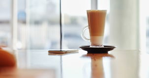 Glas des Kaffees und des Handys auf Tabelle stock video footage