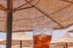 Glas des kalten Getränks gegen Sonnenschutzregenschirme Stockfoto