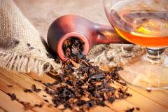 Glas des Kognaks und des Rohres mit Tabak Lizenzfreie Stockbilder