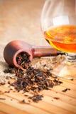 Glas des Kognaks und des Rohres mit Tabak Stockbild