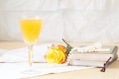 Glas des Mimosencocktails mit Weinlesebüchern und -perlen Stockfotografie